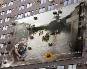 "Tο μήνυμα λέει ""Ο αέρας που δροσίζει το σπίτι σας, υπερθερμαίνει τη γη"". Η παραπάνω φωτογραφία προέρχεται από μια αφίσα εταιρίας ενδυμάτων και έχει τοποθετηθεί στην εξωτερική πλευρά ενός κτηρίου. Στην φωτογραφία παρατηρούμε πρόσφυγες που τρέπονται σε φυγή από τις πλημμύρες στην Ασία, θέλοντας να περάσει το μήνυμα ότι ένας από τους λόγους του φαινομένου του θερμοκηπίου είναι και η υπερβολική παραγωγή διοξειδίου του άνθρακα στην ατμόσφαιρα που προκαλείται και από την χρήση κλιματιστικών."